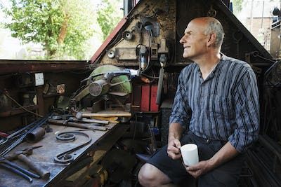 Blacksmith sitting on a working narrowboat on a waterway, in his workshop holding mug.