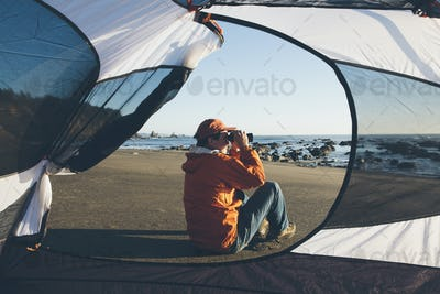 Man framed by camping tent, sitting on beach and looking through binoculars at dusk, Olympic