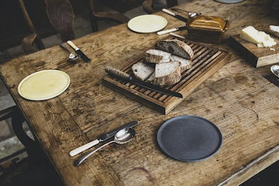 High angle close up of plates, cutlery and bread on a vintage wooden table.