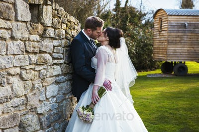 A bride and groom kissing on their wedding day standing in a garden.