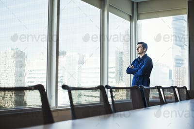 A man standing with arms crossed in a meeting room looking out of a window at an urban landscape.