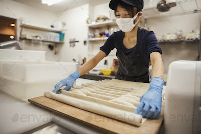 Woman working in a bakery, wearing protective gloves and mask, placing dough on large wooden board.