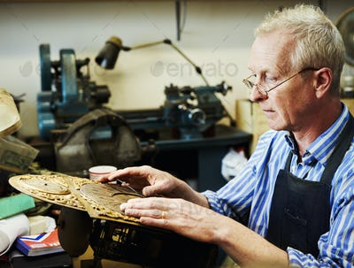 A clock maker adjusting the hands on the face of an antique clock.