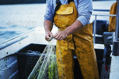 A fisherman in yellow waders on his boat holding the fishing net.