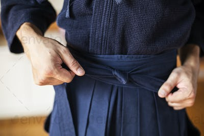 Close up of Kendo fighter tying belt of blue Kendo uniform.