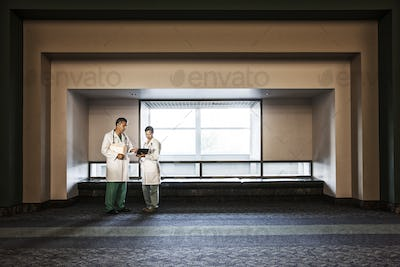 Caucasian man doctor and asian woman doctor conferring in hospital hallway.