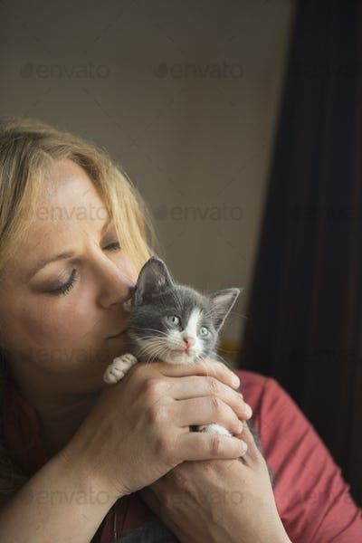 Woman holding a small grey and white kitten in her two hands, nuzzling it.