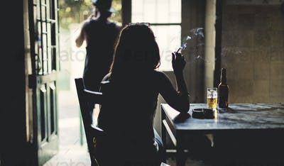 Rear view silhouette of woman sitting indoors at a table, smoking cigarette, beer glass and bottle