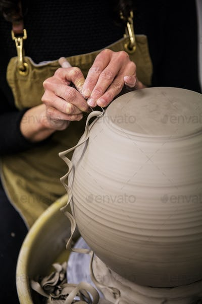 Close up of potter wearing apron working on spherical clay vase on pottery wheel.