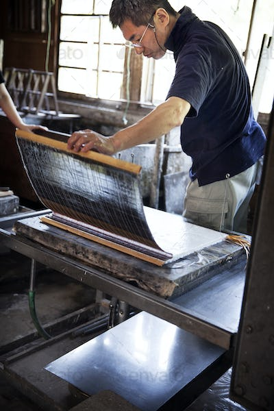 Japanese man holding a paper frame and inspecting fresh piece of traditional Washi paper.