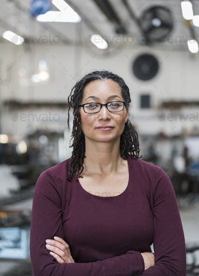 Woman with brown hair wearing glasses standing in metal workshop, smiling at camera.