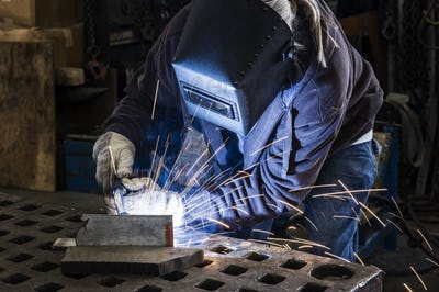 Factory worker using Oxyacetylene gas to weld two piece of metal in a sheet metal factory