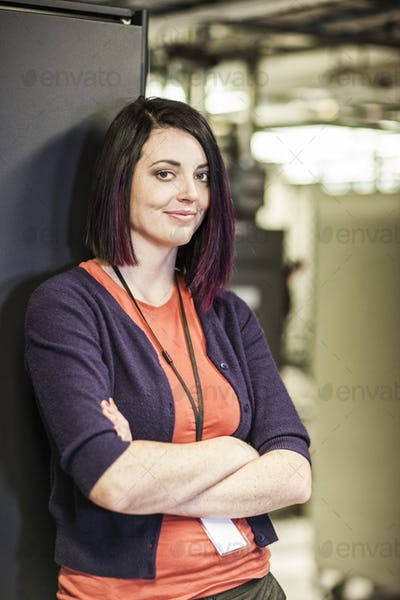 Caucasian woman technician in a large computer server farm.