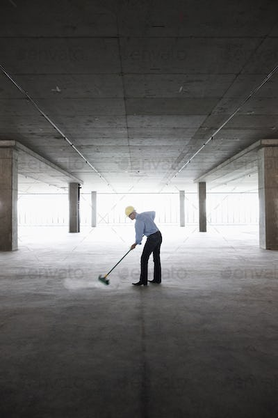 Asian businessman cleaning up with a broom in a large empty raw office space.