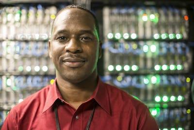 Black man technician in a computer server farm.