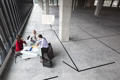 Asian architect with caucasian man and woman planning workspace in a new raw office location.