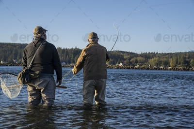 A guide advises his client while fly fishing in salt water for searun coastal cutthroat trout and