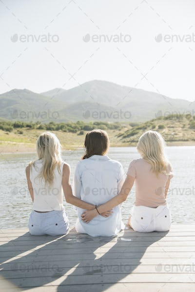 Rear view of a mother and her two blond daughters sitting on a jetty.