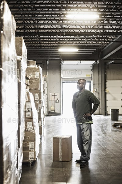 African American male waehouse worker checking inventory on stacks of cardboard boxes holding