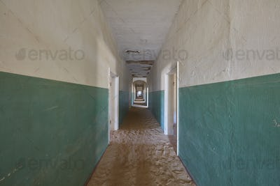 A view down a long corridor in a deserted derelict building full of sand.