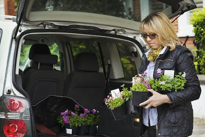 Woman wearing sunglasses standing at back of estate car with open hatch, holding plastic flower