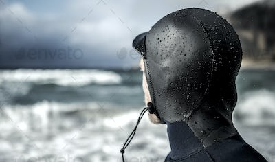 Rear view of the head of a surfer wearing a wetsuit looking out to sea.