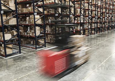 Blur of a motorized stock picker between aisles of cardboard boxes on pallets stacked on large racks