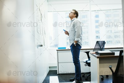 A man standing in an office looking at pieces of paper pinned on a whiteboard.