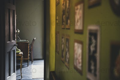 View along corridor with vintage pictures on green wall, open brown wooden door to study with