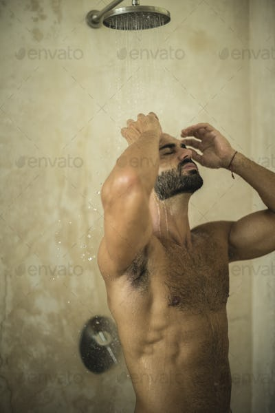 A man standing in a shower in a bathroom.