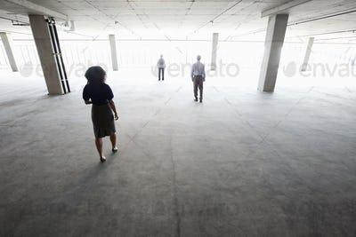 Business people walking toward windows in a large empty office raw space.