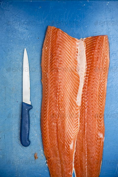 High angle close up of fillets of fresh salmon and knife on blue chopping board.