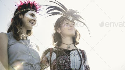 Two young women at a summer music festival faces painted, wearing feather headdresses.