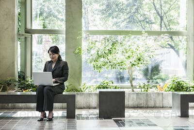 Asian businesswoman working in a large open lobby area.
