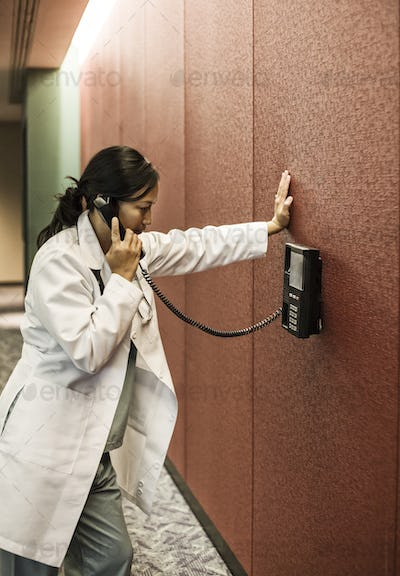 Asiasn woman doctor on a phone in a hospital lobby.
