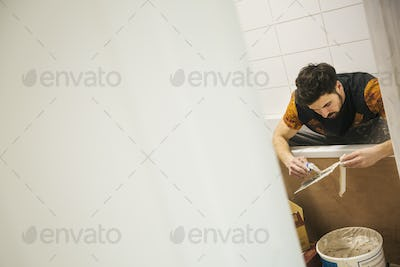 A builder, tiler working in a bathroom, spreading adhesive on a tile.