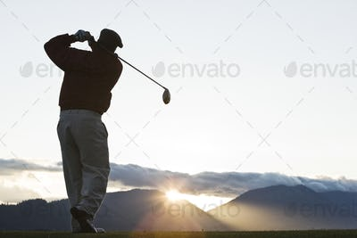 A golfer teeing off at sunrise.