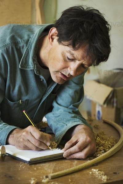 A craftsman using pencil and paper to do calculations and measurements on a workbench, among the