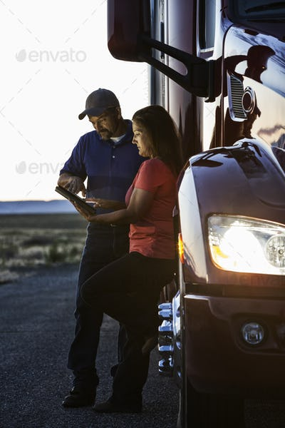 Husband and wife driving team checking their notebook computer log while standing next to the cab of