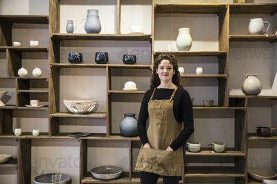 Woman with curly brown hair wearing apron standing in her pottery shop, smiling at camera.