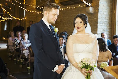 A bride and groom at their wedding ceremony, standing side by side in front of the wedding guests.