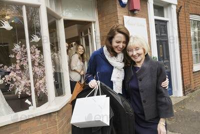 Two women with shopping bags hugging on the street outside a wedding dress shop