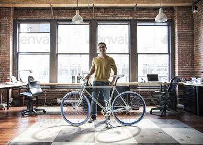 Hispanic man at his office workstation with a bicycle.