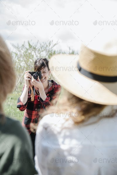 A photographer taking pictures of two women on a summer's day.