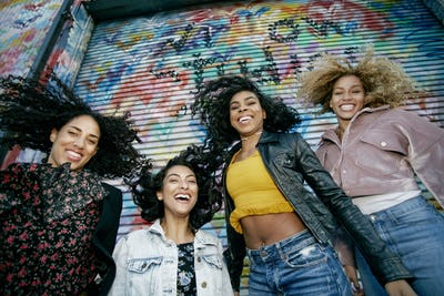 Low angle view of four young women with curly hair standing in front of shutter covered in colourful
