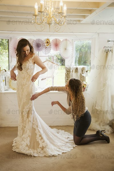 A dressmaker taking in a wedding dress, pinning and fitting it to the client, a young woman. A bride