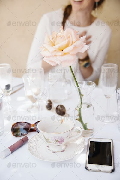 Close up of a rose in a vase on a table with cups and glasses, a cell phone and sunglasses.