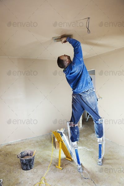 A plasterer wearing stilts smoothing fresh plaster high up on the walls of a house under