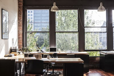 Creative office interior. View through a window to trees and city buildings.