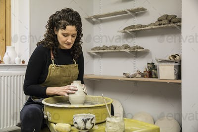 Woman with brown curly hair wearing apron shaping clay vase on pottery wheel.